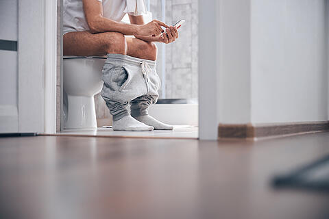Man using his gadget in the water closet
